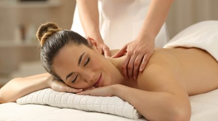 Portrait of a relaxed lady receiving a massage in a spa interior