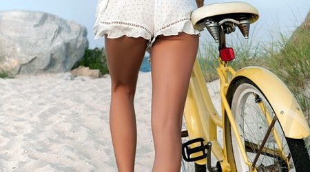 Beautiful woman with bike on the beach. Summer vacation