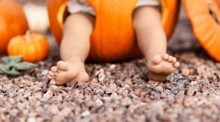 Closeup of baby legs inside orange pumpkin at Halloween, season holiday concept - Image