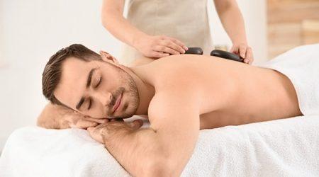 Handsome man receiving hot stone massage in spa salon