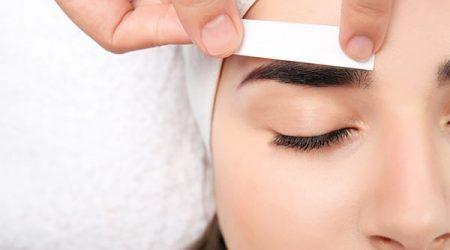 Young woman having professional eyebrow correction procedure, closeup