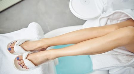 Top view close up of female legs in white flip-flops lying above bath in chair for nail service