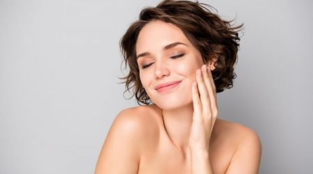 Portrait of positive lovely pretty girl touch hand face enjoy her soft pure, perfect skin after bodycare plastic surgery treatment isolated over grey color background