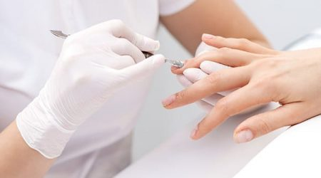 Hands of manicurist pushing cuticles on female's nails with manicure tool. Woman receiving manicure and nail care procedure
