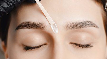 Master wax depilation of eyebrow hair in women, brow correction.
