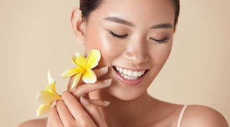 Beauty. Model With Flower Portrait. Happy Ethnic Woman With Exotic Plumeria Near Face Against Beige Background. Asian Girl With Nude Makeup, Healthy, Smooth And Glowing Facial Skin.