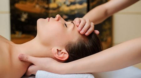 Spa procedure of neck massage. Close up view of beautiful young woman lying on back. Masseur /therapist massaging her face