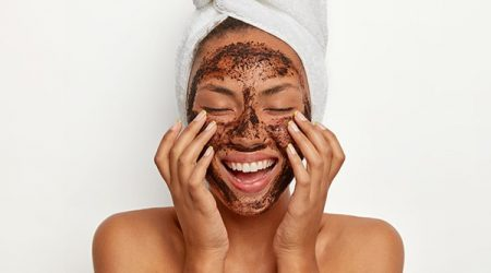 Portrait of cheerful smiling dark skinned woman applies natural coffee mask, makes circular motions with hands and massages skin, stimulates facial blood supply, wears wrapped towel on head.