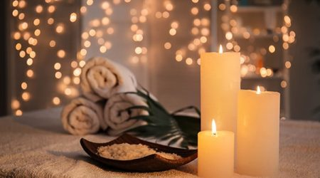 Plate with sea salt and burning candles on table in spa salon