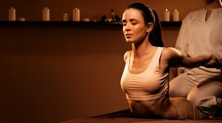 Young pretty woman has Thai massage at luxury spa. Warm inviting colors, calm atmosphere, charming light. Concept of serene spa treatments. Copy space