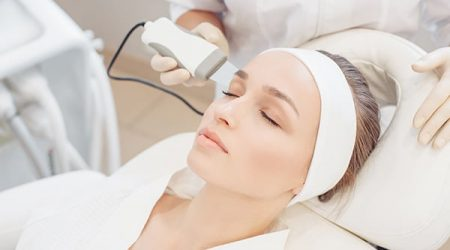 Close-up cosmetologist making ultrasound hardware cleaning of the face of her patient a beautiful young woman. Concept skin cleansing and restoration of elasticity