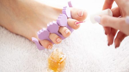 Woman's french pedicure. Close Up Woman Hands Touching Long Legs, Soft Skin. Hair Removal.