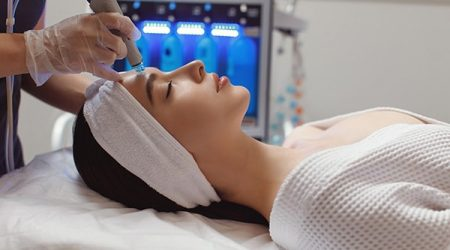 Side view of woman receiving microdermabrasion therapy on forehead at beauty spa. Hydrafacial procedure in Cosmetology clinic.