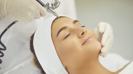 Facial skincare treatment. Young smiling womans face getting oxygen therapy or jet peeling from cosmetologist with special equipment in beauty spa salon