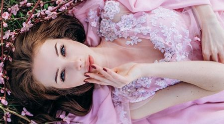 Girl in a pink flowered garden of peaches in a pink dress and makeup.