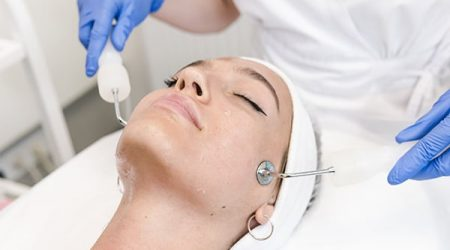 The young female client of cosmetic salon having microcurrent procedure on her face with special devices, close-up. Beautician using electrical impulses for facial procedures. Concepts of skin care product and beauty salon or clinic.