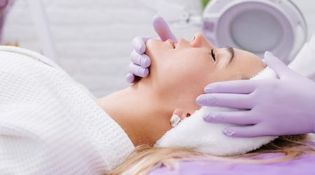A beautician make face massage to the patient in the beauty salon