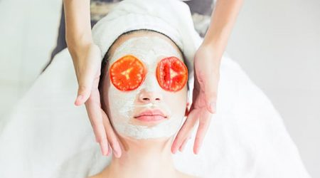 Red Tomato slice on eyes, relax spa background, health and beauty concept, beauty woman is relaxing facial by handy massage.