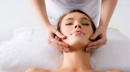 female masseur doing facial massage to client in spa salon