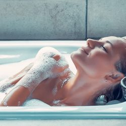 Portrait of a woman with closed eyes of pleasure taking bath at home, female with pleasure enjoys bath with a foam, a day at spa, hygiene and relaxation concept