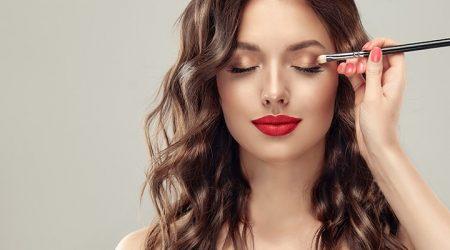 Makeup artist applies  eye shadow  . Beautiful woman face. Hand