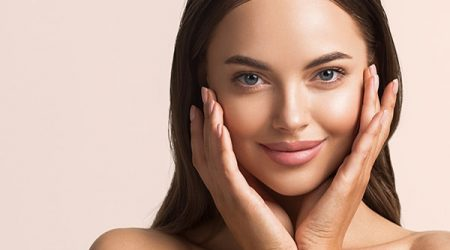 Beautiful woman face close up natural make up hand touching face